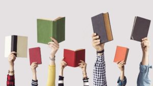 Hands holding up books at different heights