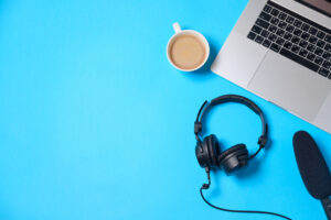overhead view of a laptop with a coffee and headphones