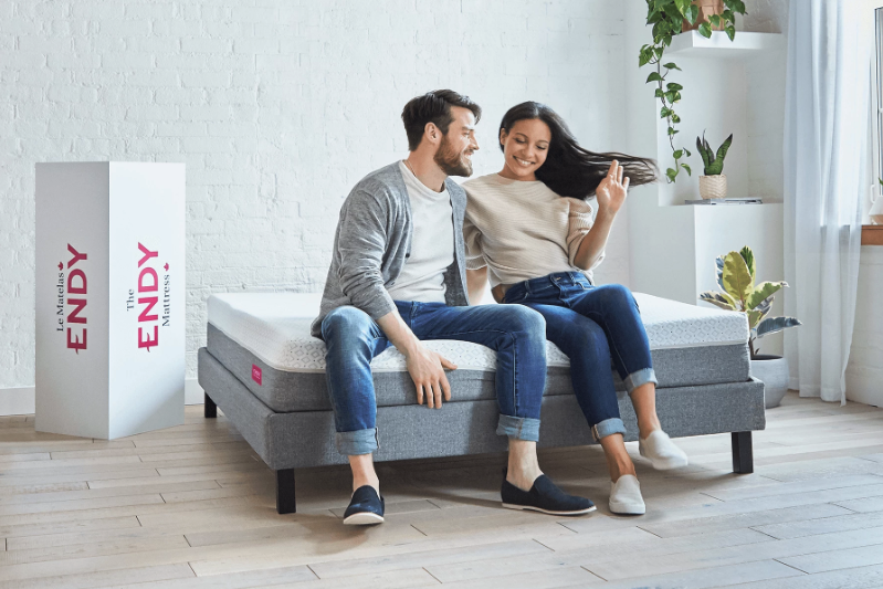 a man and woman sit on an Endy mattress