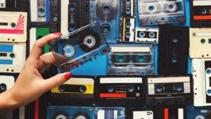 A hand picking a cassette tape for the best background music for videos.