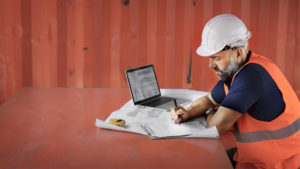 Photo of a man in a hard hat working on paperwork on a construction site
