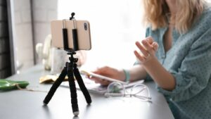 woman uses a smartphone and tripod for remote video recording
