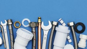 photo of pipes, wrenches, and other building supplies on a blue backdrop