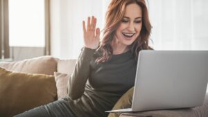 woman waves at her computer to make her video messaging personal
