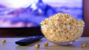 Popcorn and Remote Control in front of a tv screen