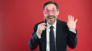 Photo of a man dressed in a suit holding up pink novelty glasses shaped like stars