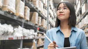 a woman working in procurement walks through a warehouse